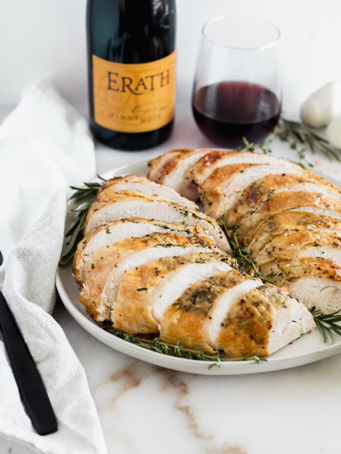 sliced herb roasted turkey breast with a bottle and glass of wine in the background.