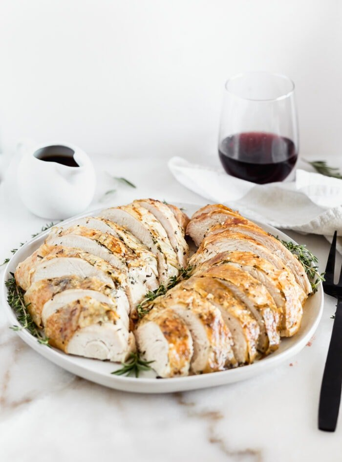 sliced herb roasted turkey breast on a grey platter wtih a glass of red wine in the background.