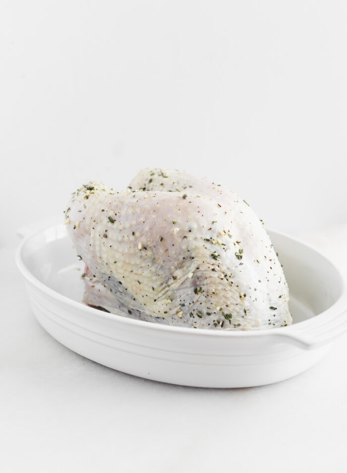 raw turkey breast rubbed with herbs in a white baking dish.