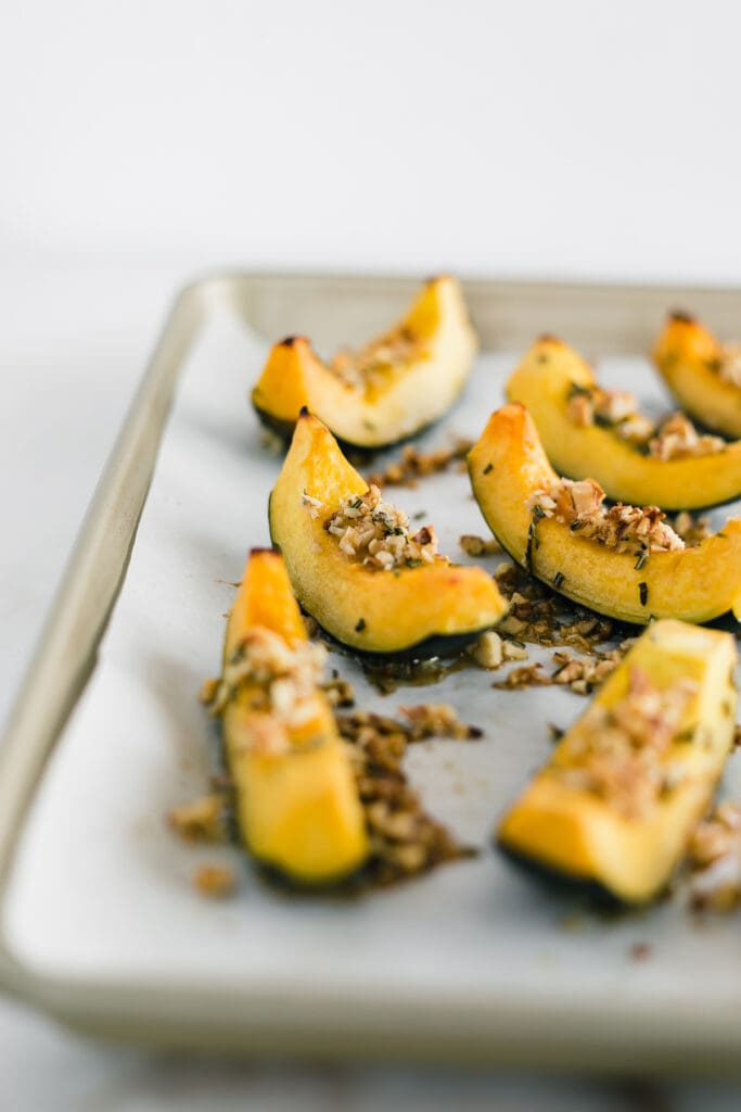 roasted acorn squash wedges topped with walnut topping on a baking sheet lined with parchment paper.