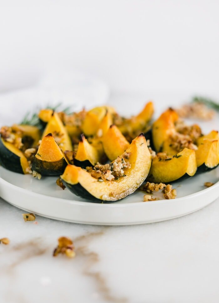 maple rosemary roasted acorn squash wedges with walnut topping on a white plate.