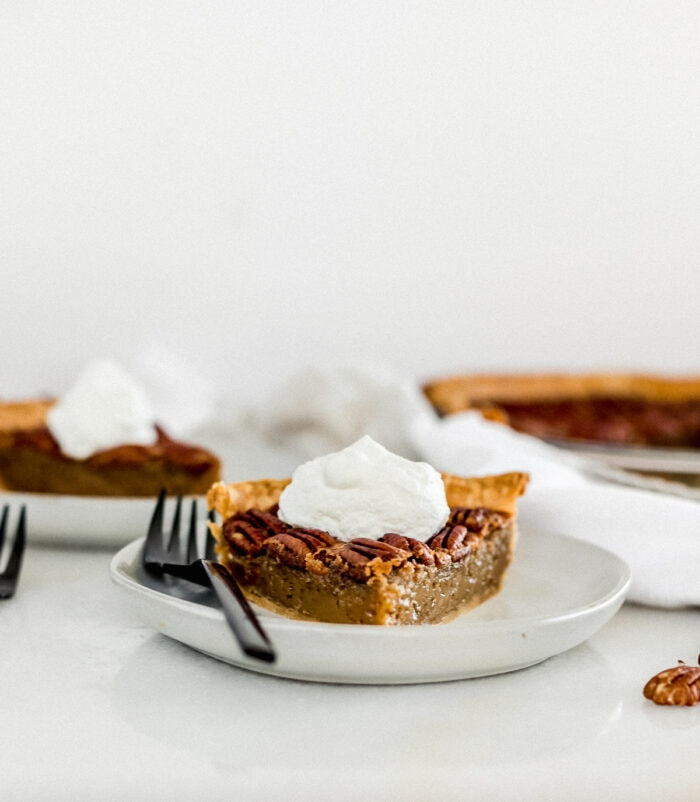 slice of pecan pie topped with whipped cream on a grey plate with a black fork.