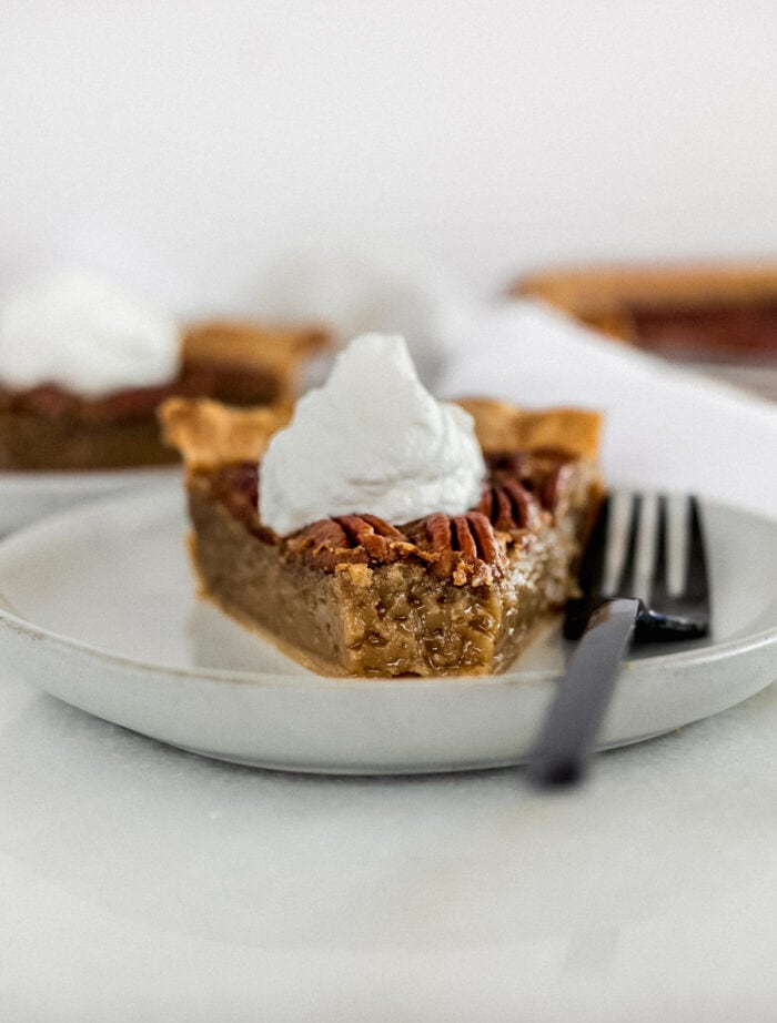 slice of pecan pie topped with whipped cream on a grey plate with a black fork with a bite taken out.