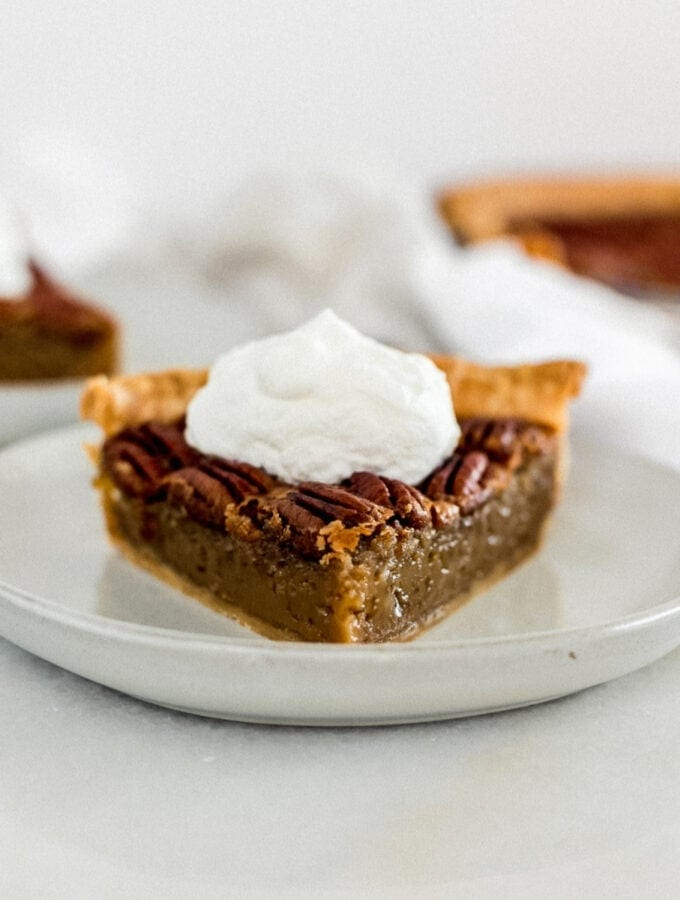 slice of pecan pie on a grey plate topped with whipped cream.