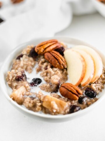 bowl of apple cranberry oatmeal topped iwth apple slices and pecans.