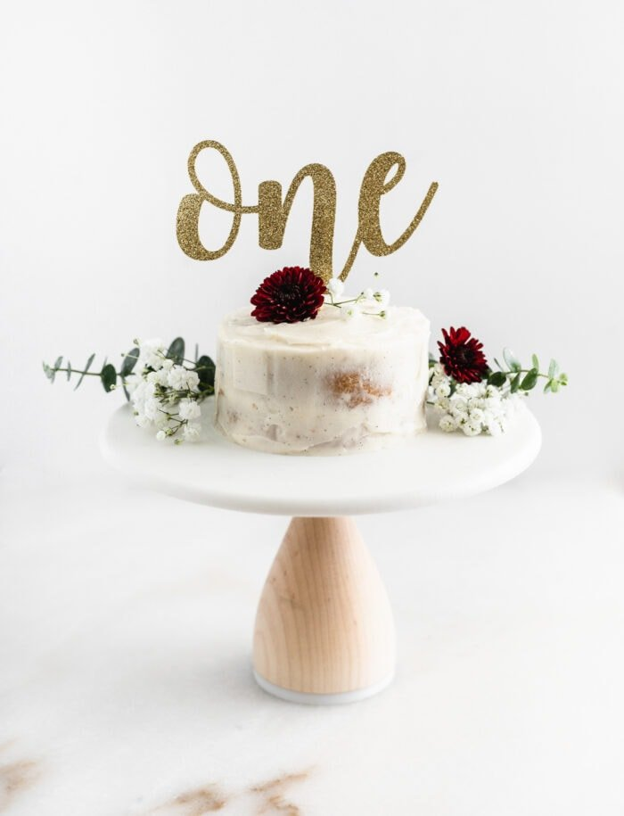 white smash cake on a white stand, topped with flowers and a one cake topper.