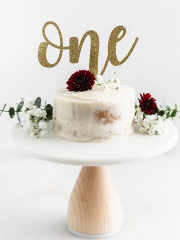smash cake topped with flowers on a white cake stand.