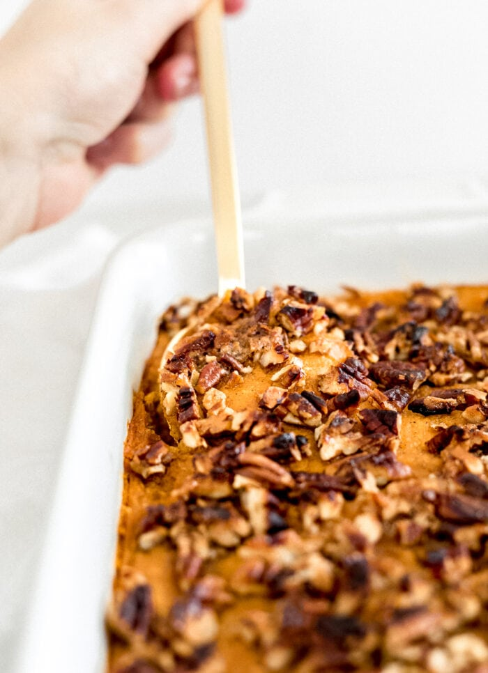 gold spoon digging into sweet potato casserole topped with pecans.
