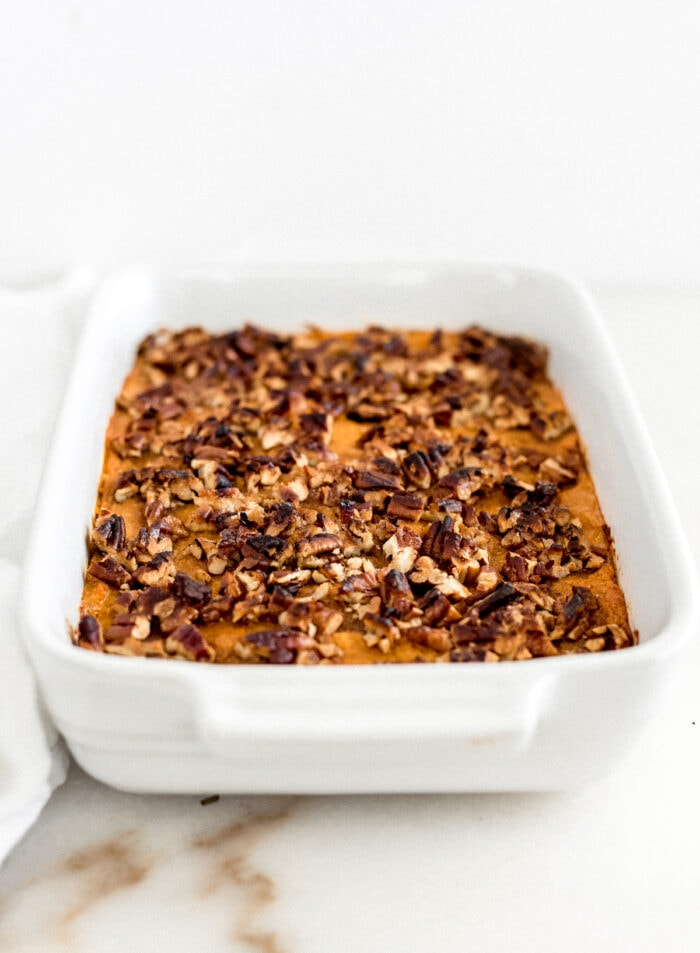 baked sweet potato casserole with pecan topping in a white baking dish.