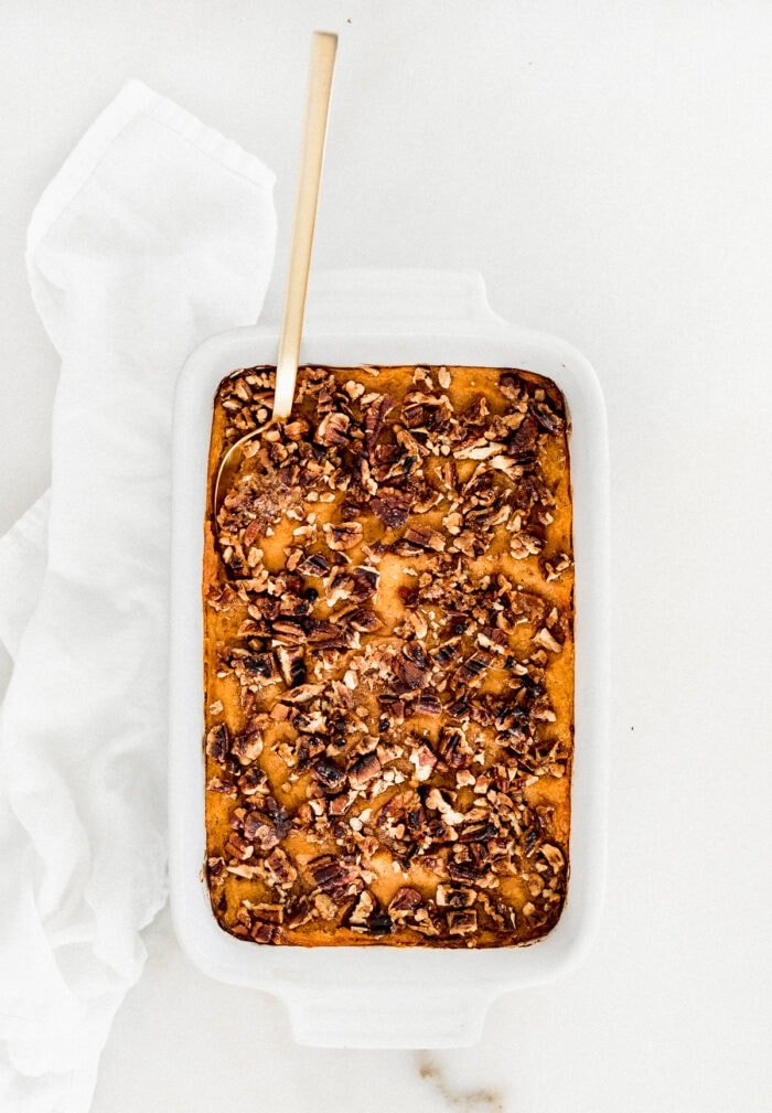 overhead view of sweet potato casserole in a white dish with a gold spoon in it.