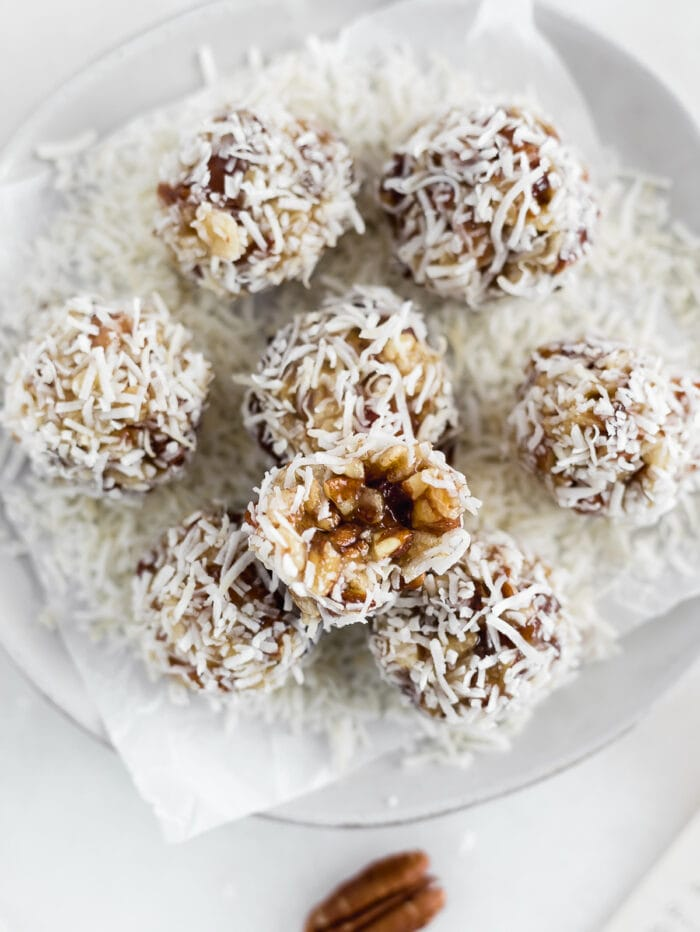 overhead view of coconut date balls on a plate with a bite taken from one.