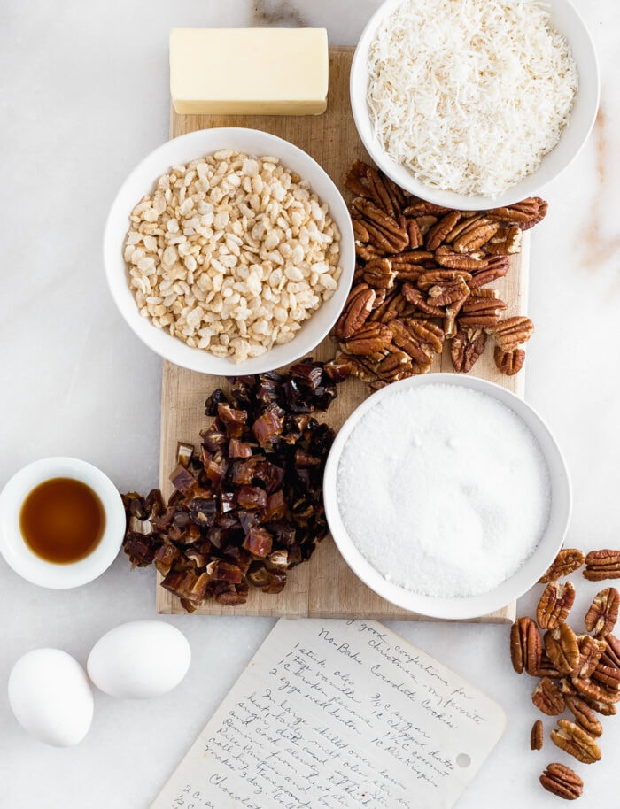 Ingredients for no bake coconut date cookies on a white marble background with a handwritten recipe card.