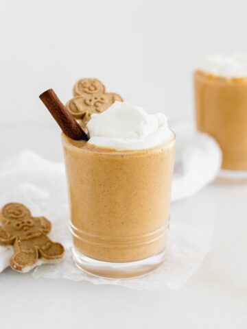 gingerbread smoothie in a glass topped with whipped cream and a gingerbread man.