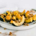 wedges of roasted acorn squash with maple rosemary walnut topping on a white plate.