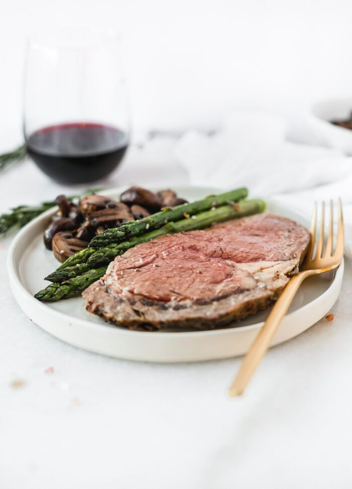 sliced prime rib on a white plate with asparagus and mushrooms with a gold fork.