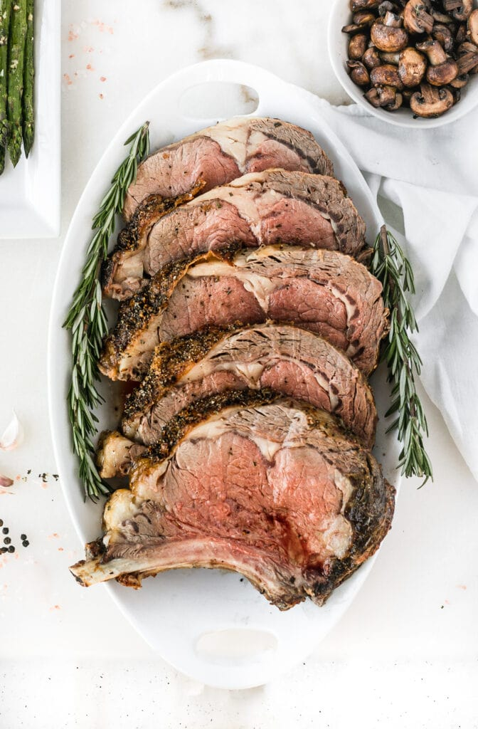overhead view of carved prime rib roast on a white platter with rosemary sprigs.
