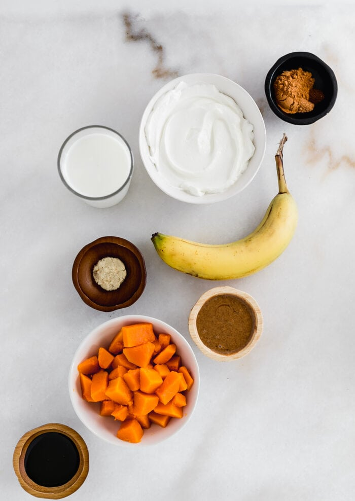 overhead view of ingredients for gingerbread sweet potato smoothie on a white background.