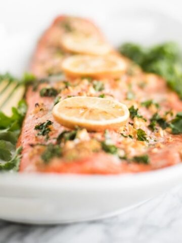 salmon with lemons on top on a white platter.