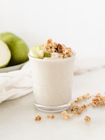 pear crisp smoothie in a glass topped with granola, with pears in the background.