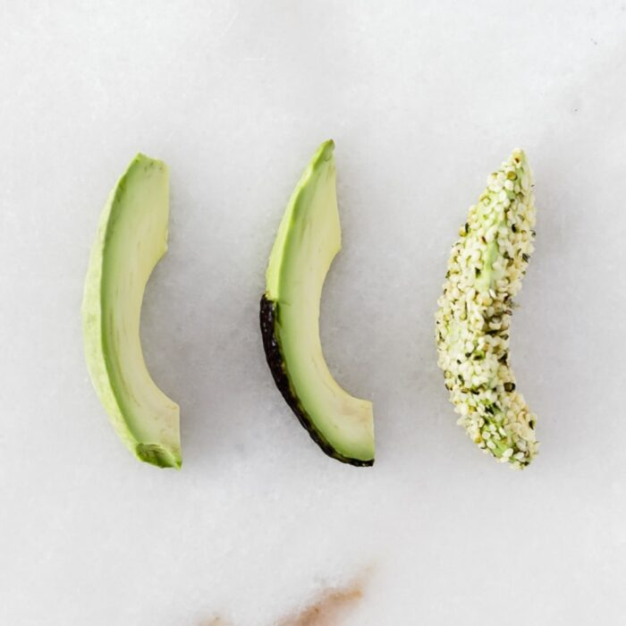 three slices of avocado, one plain, one with skin on half, and one rolled in hemp seeds.