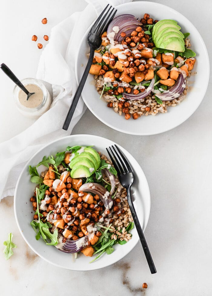 overhead view of two maple roasted chickpea grain bowls with roasted sweet potatoes, onions, arugula, and avocado with tahini dressing in white bowls with black forks in them.