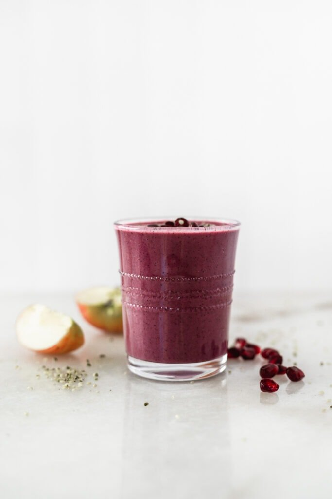 apple berry pomegranate smoothie in a glass surrounded by pomegranate arils and apple slices.