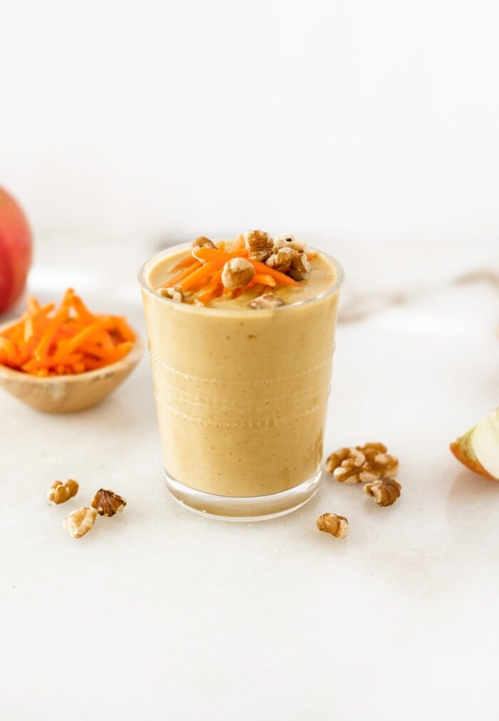 carrot cake smoothie in a glass topped with shredded carrots and walnuts.