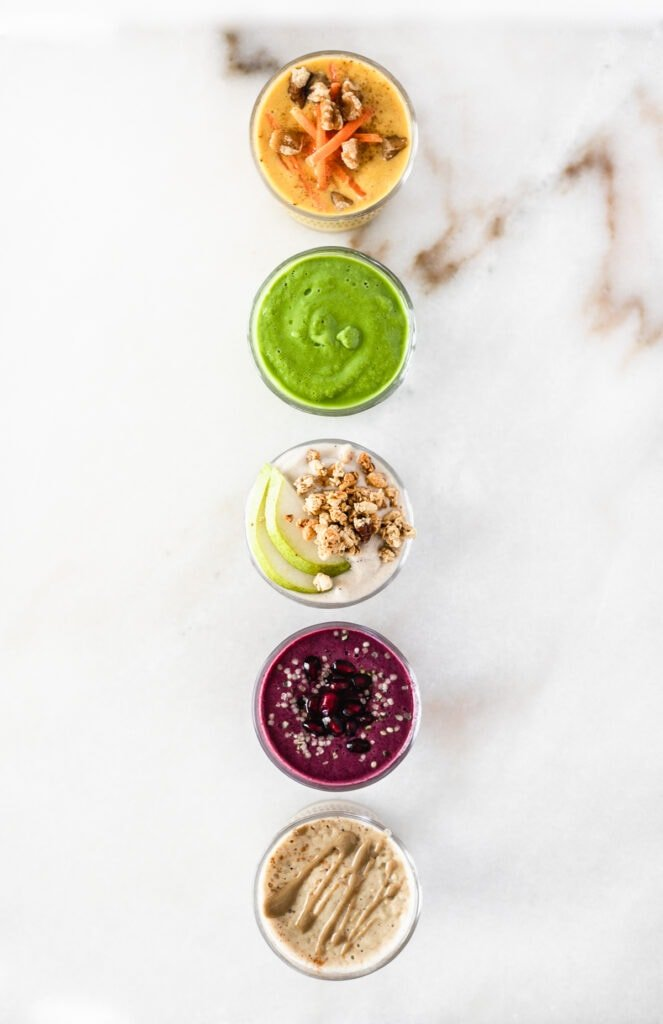 overhead view of 5 smoothies in a straight vertical line.