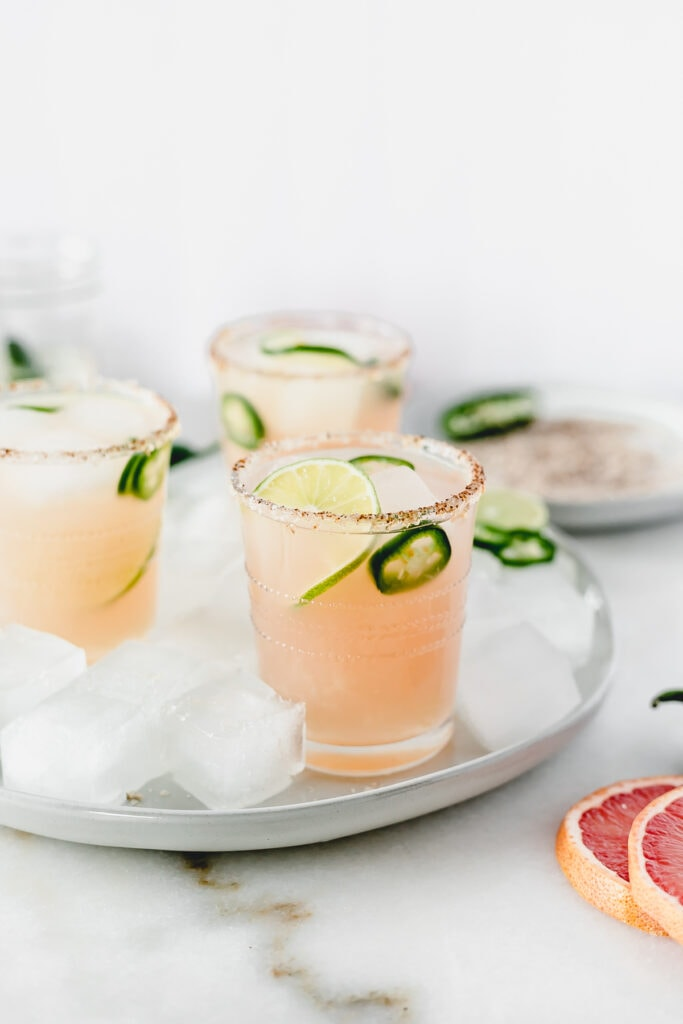 three mezcal paloma cocktails with jalapeno slices and limes in them sitting on a grey plate with ice with a plate of smoked salt in the background.