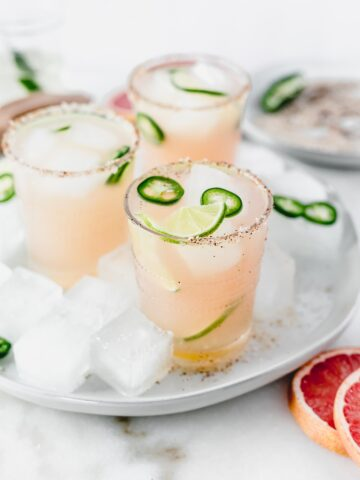 three mezcal paloma cocktails with jalapeno slices and limes in them sitting on a grey plate with ice.