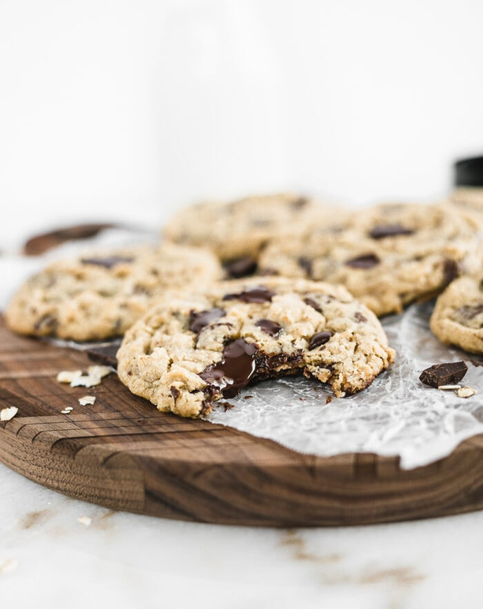 oatmeal chocolate chip cookie with a bite taken out on a wooden board with more cookies in the background.