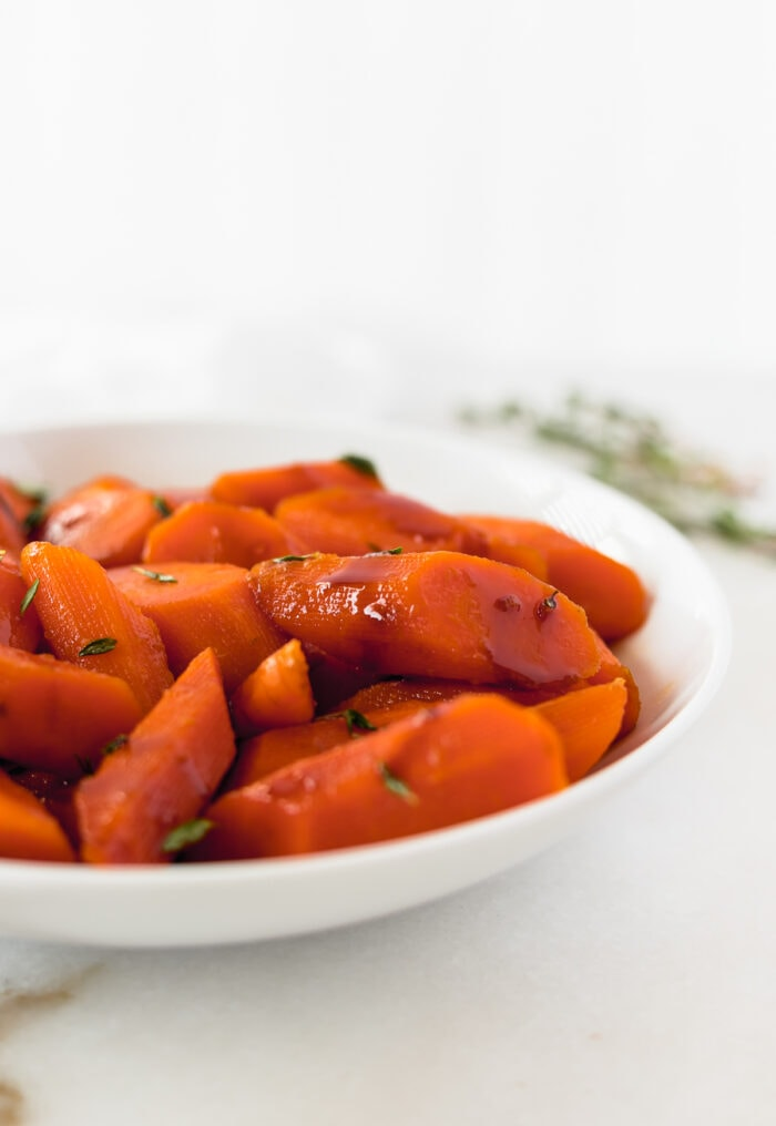 balsamic glazed carrots with thyme in a white bowl.