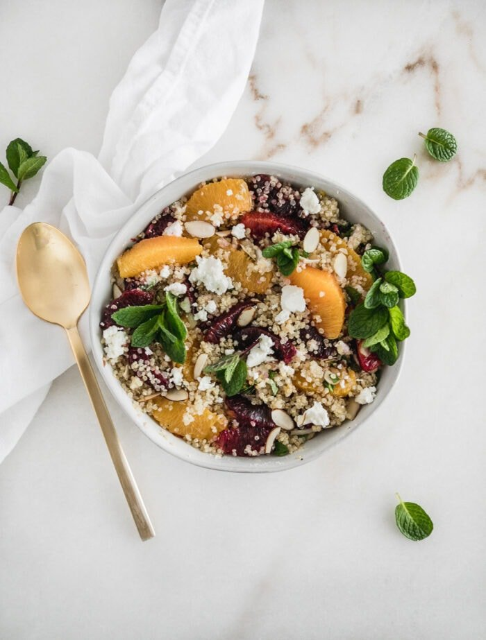 overhead view of quinoa salad with blood oranges, navel oranges, mint and goat cheese in a bowl with a gold fork beside it.