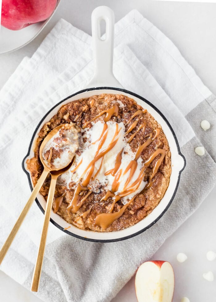 overhead view of a mini apple snickerdoodle skillet cookie topped with ice cream and caramel in a white skillet with two gold spoons in it.