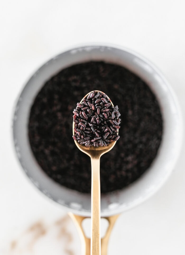 cooked black rice on a gold spoon above a pot of black rice.