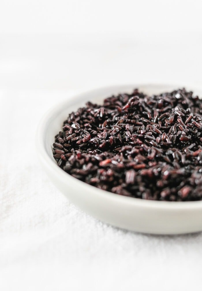 cooked black rice in a small grey bowl.