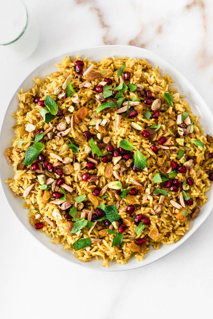 jeweled rice with pomegranate and herbs on a large plate.