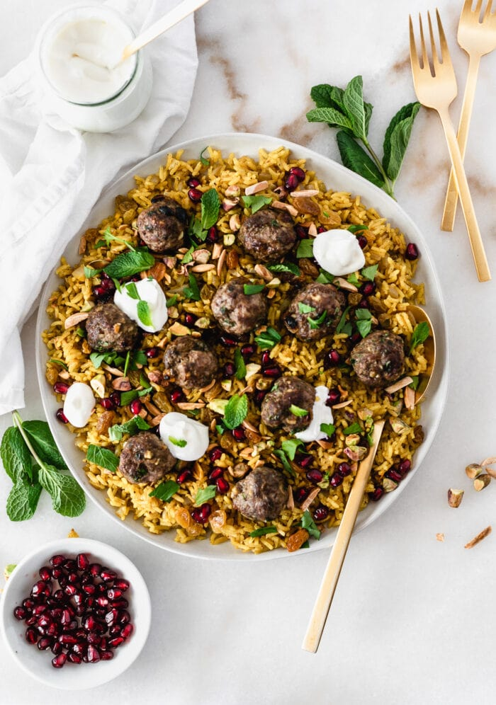 overhead view of jeweled rice with lamb meatballs and dollops of yogurt on top on a large plate with a gold spoon in it.
