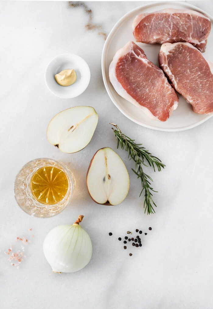 overhead view of ingredients needed to make pan seared pork chops with pears and bourbon on a white background.
