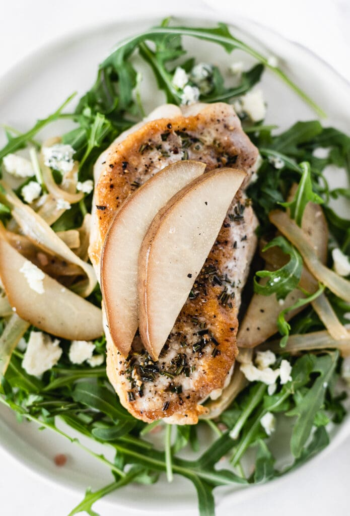 overhead view of a seared porj chop with pears and onions on top of a bed of arugula.