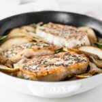 rosemary crusted pork chops with pears and onions in a white cast iron skillet.