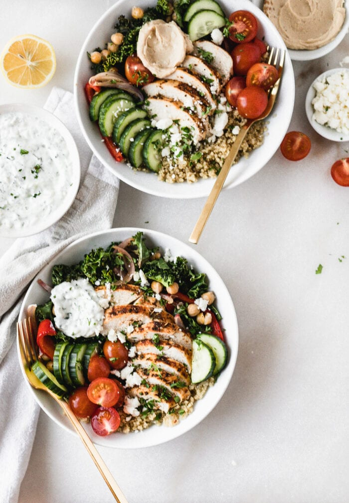 overhead view of two greek chicken grain bowls with gold forks on a white background.