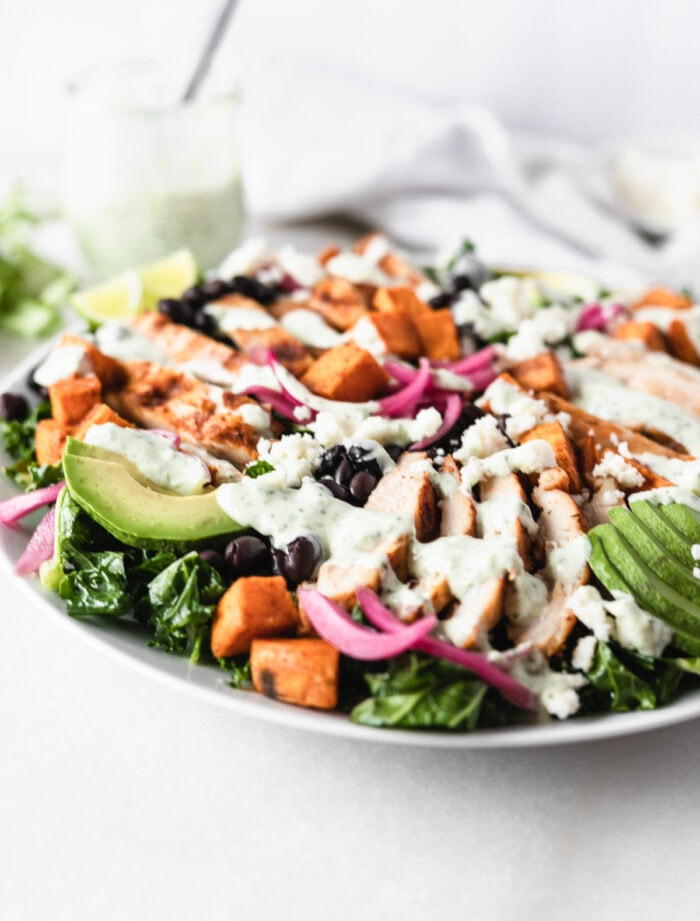 grilled chicken and sweet potato kale salad drizzled with creamy dressing.