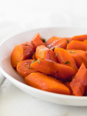 closeup of carrots in a white bowl with thyme and balsamic glaze.