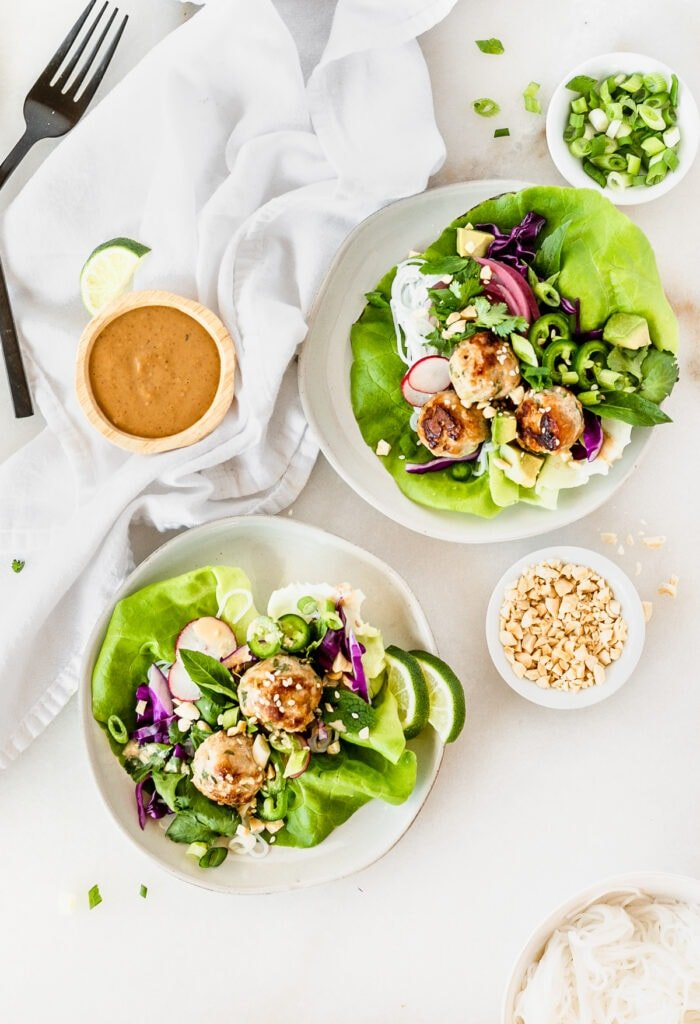 overhead view of two pork meatball lettuce wraps on small plates surrounded by small bowls of peanut dipping sauce, chopped peanuts, and green onions on a white background.