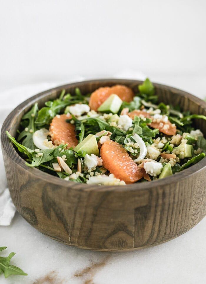 cara cara orange arugula salad in a wooden bowl.