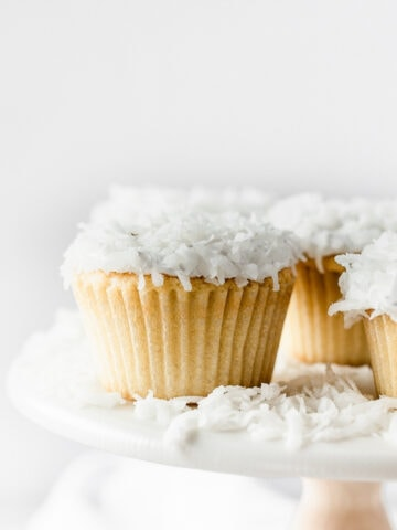 closeup of a coconut cupcake on a white cake stand with other coconut cupcakes.