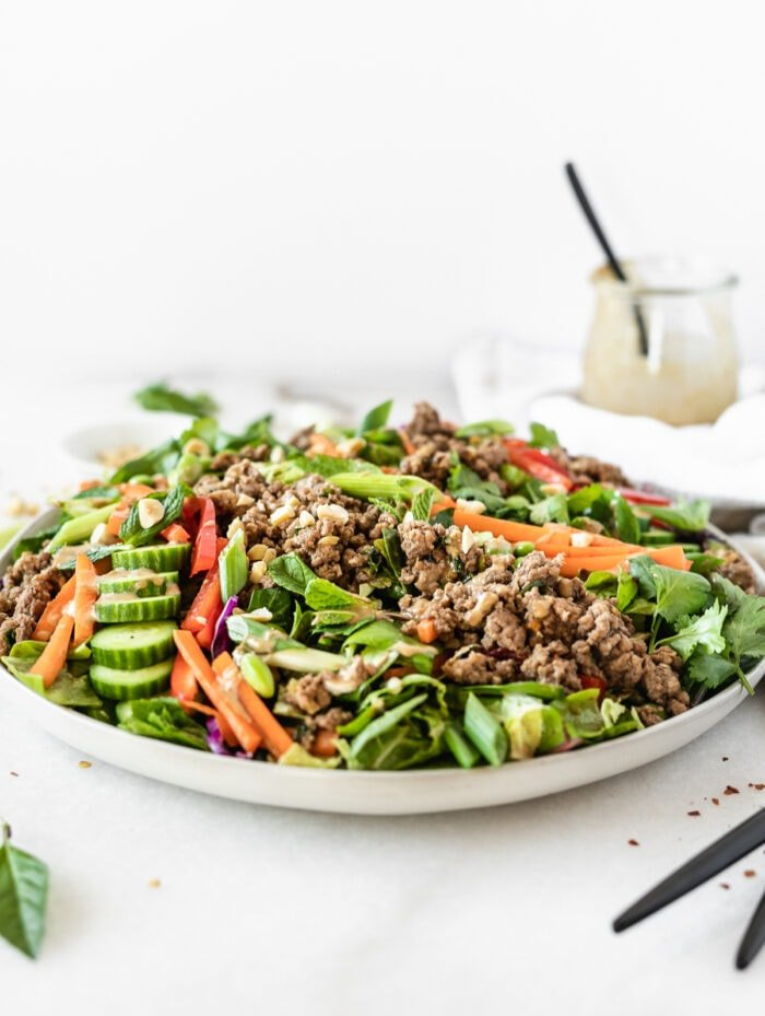 thai ginger ground beef salad on a grey plate with a jar of peanut sauce in the background.