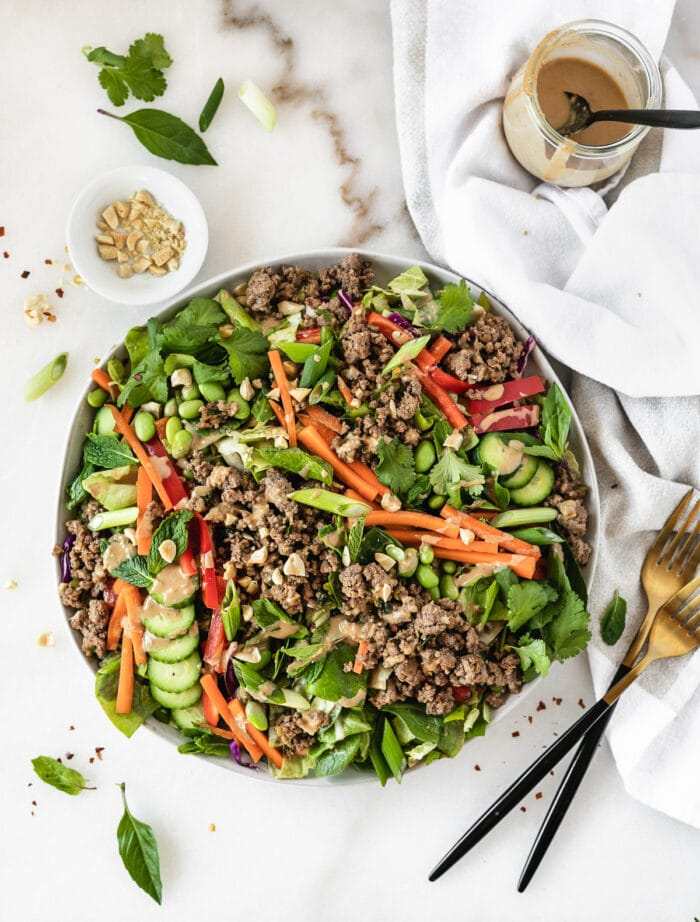 overhead view of thai ginger ground beef salad with a bowl of chopped peanuts and two gold and black forks beside it.