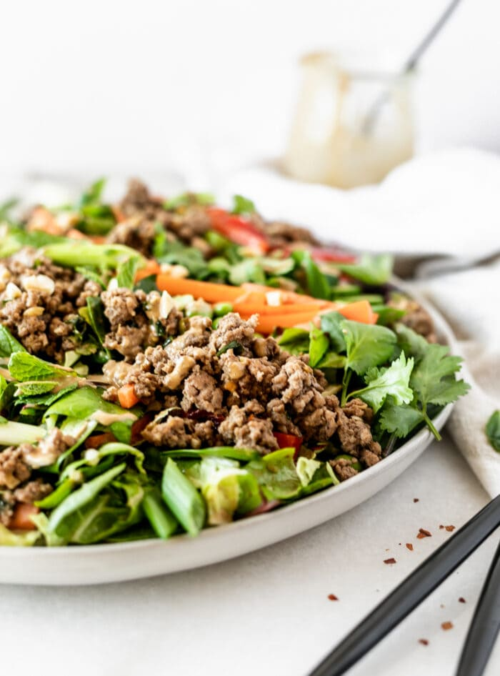 closeup of thai ginger ground beef salad on a grey plate.